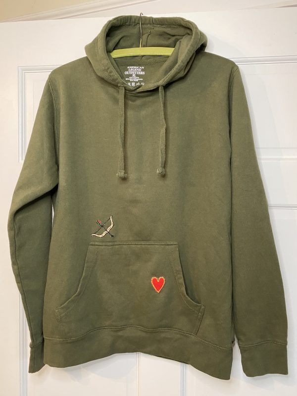 green hoodie with vintage bow and arrow and heart appliqués